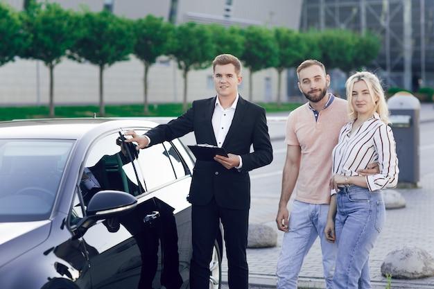 Молодой автосалон в деловом костюме показывает покупателям новую машину. молодая пара, мужчина и женщина, покупают машину. покупка машинки, тест-драйв.