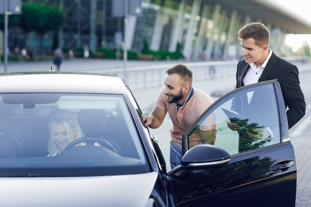 Молодой автосалон в деловом костюме показывает покупателям новую машину. молодая пара, мужчина и женщина, покупают машину. женщина, сидящая за рулем. покупка машинки, тест-драйв.