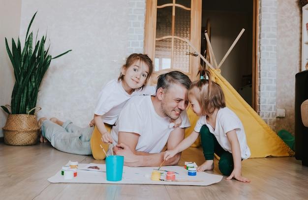 Молодой заботливый отец учится рисовать вместе с маленькими дочерьми, мужчина лежит на полу и учит девочек рисовать цветы, предметы интерьера.