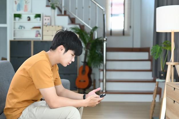 Молодой случайный мужчина использует смартфон и сидит на диване в гостиной