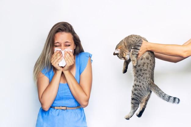 Молодая кавказская блондинка с аллергией на кошек держит платок на белом фоне