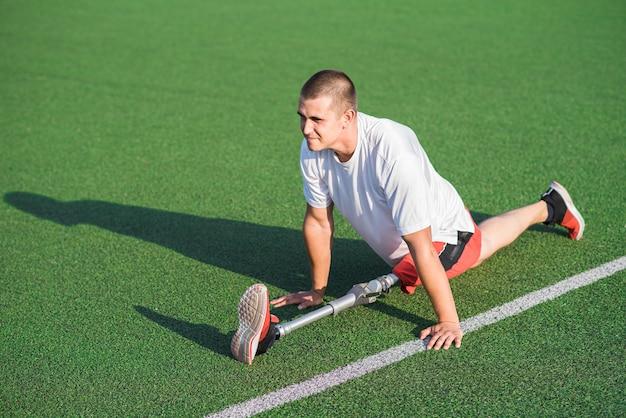 スタジアムの床にひもで座っている義足を持つ若い白人ブルネットの男。スポーツのコンセプト。