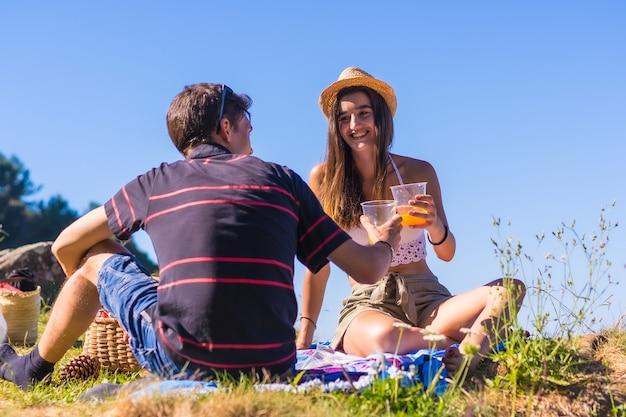 Молодая кавказская пара на пикнике пьет апельсиновый сок в горах у моря, наслаждаясь теплом
