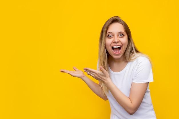 흰색 tshirt 포인트에 젊은 백인 흥분 웃는 금발의 여자 발기인은 밝은 색 노란색 벽에 고립 된 제품을 제시하는 두 손으로 텍스트 또는 디자인을위한 빈 빈 공간을 복사