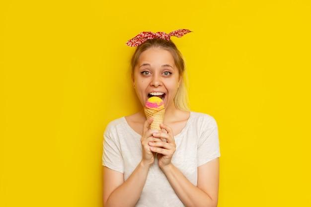 Молодая кавказская взволнованная улыбающаяся симпатичная блондинка с хвостиком и бантом ест сорбет из фруктового мороженого в вафельном рожке, изолированном на ярко-желтой стене летняя концепция