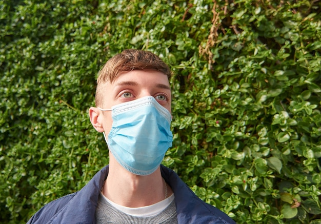 Молодой кавказский парень в санитарной маске на открытом воздухе