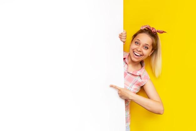 그녀의 손가락으로 화이트 빈 보드에 젊은 백인 행복 미소 예쁜 금발의 여자 포인트는 밝은 색 노란색 벽에 텍스트 또는 디자인을위한 복사 공간을 보여줍니다