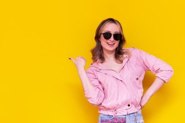 분홍색 재킷과 선글라스에 젊은 백인 행복 웃는 여자는 밝은 색상의 노란색 벽에 고립 된 그녀의 손가락 제시 제품으로 텍스트 또는 디자인 복사 빈 빈 공간을 나타냅니다
