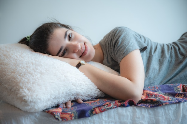 젊은 백인 여성은 침대에서 순간을 즐기고, 편안하고 완전히 휴식을 취한 웃는 소녀, 일출 햇살이 아침에 일어납니다.