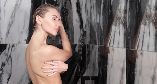 젊은 백인 여성이 샤워 실에 서서 눈을 감고 꿈을 꾸었습니다. 젖은 머리. baner,