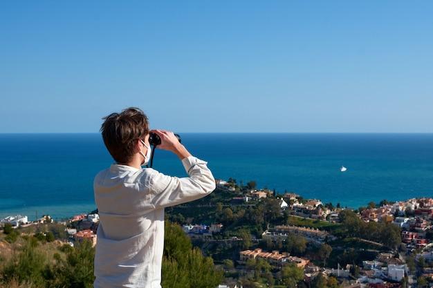 Молодой кавказский мужчина смотрит на море в бинокль