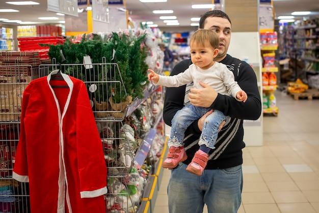 Молодой кавказский мужчина держит на руках маленького симпатичного малыша в магазине возле книжного шкафа. детские очки с пальцем на рождественский костюм санта-клауса и новогодние украшения. крупный план, мягкий фокус, размытие фона