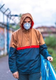 강 공원을 산책하는 마스크에 젊은 백인 남자. 통제되지 않은 covid-19 전염병의 첫 걸음