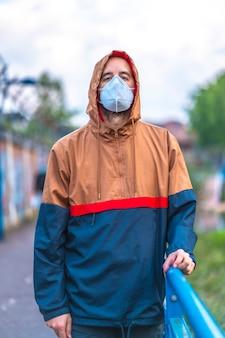 공원을 산책하는 마스크에 젊은 백인 남자. 통제되지 않은 covid-19 전염병의 첫 걸음