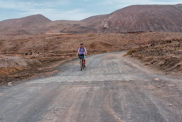 Молодой белый мужчина спереди едет на велосипеде по грязной дороге в ла-грасиоза, канарские острова