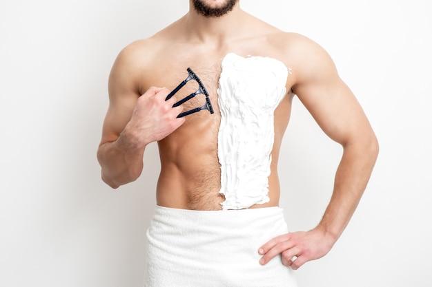 ひげを生やした若い白人男性が、白い背景に胸を剃るためにかみそりを持っている