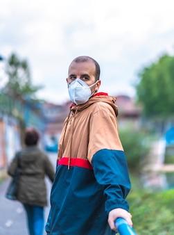그의 첫 번째 산책 중 하나에 마스크와 젊은 백인 남자. 통제되지 않은 covid-19 전염병의 첫 걸음