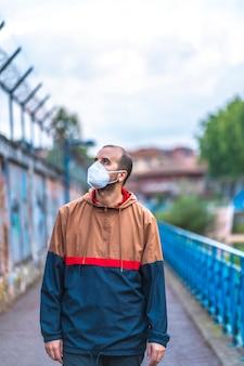 그의 첫 번째 중 하나에 마스크와 젊은 백인 남자는 자신감의 부족에서 산책. 통제되지 않은 covid-19 전염병의 첫 걸음