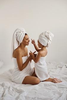 젊은 백인 어머니와 하얀 목욕 수건에 싸서 머리를 가진 작은 딸은 어머니 얼굴에 클레이 마스크를 적용