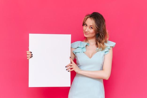 젊은 백인 예쁜 사랑스러운 여자 발기인은 밝은 색상의 분홍색 벽에 텍스트 또는 디자인을위한 빈 복사본 공간이있는 화이트 보드를 보유하고 있습니다.