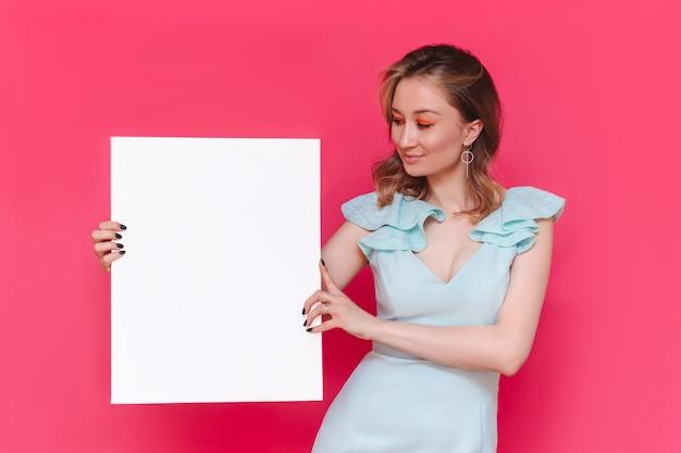 젊은 백인 꽤 웃는 여자 발기인은 밝은 색상의 분홍색 벽에 텍스트 또는 디자인을위한 빈 복사본 공간이있는 화이트 보드를 보유하고 있습니다.