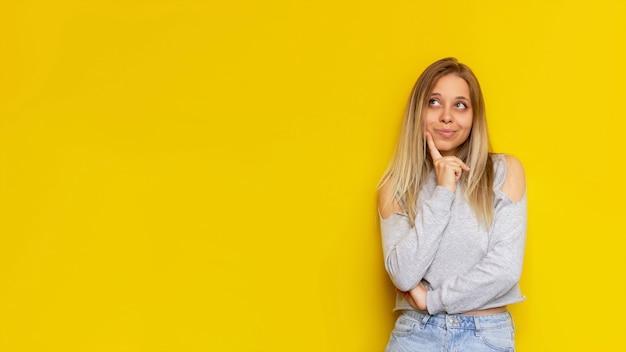 若い白人のかなり思慮深い金髪の女性が、明るい色の黄色い壁にテキストやデザイン用の空のコピー スペースを見て何かを考えている Premium写真