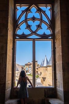 Молодая кавказская женщина занимается сельским туризмом в средневековом городе и его красивом замке