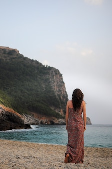長いカラフルなドレスを着た若い白人女性がビーチを歩いています背面図