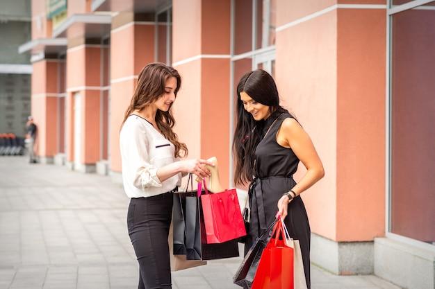 야외 쇼핑몰 근처에 서있는 그녀의 친구와 함께 새 신발 구매를 공유하는 젊은 백인 여자