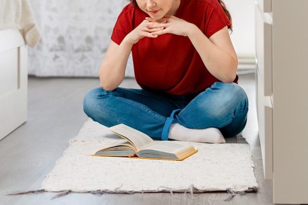 Молодая кавказская женщина сидит на полу, скрестив ноги, с интересом читает книгу.
