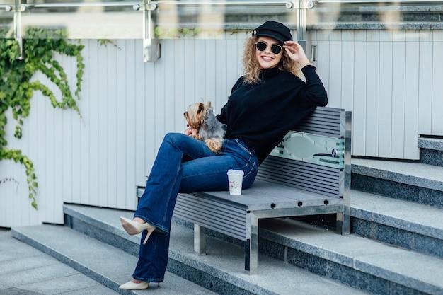Молодая кавказская женщина гуляет по европейской улице с маленькой двухцветной собакой породы чихуахуа на поводке. пасмурная теплая осенне-весенняя погода. девушка в черной рубашке и туфлях телесного цвета.