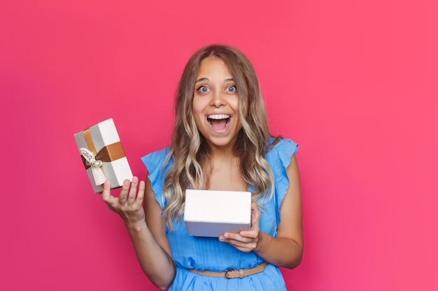 Юная очаровательница поражена взволнованной блондинкой довольна полученным подарком на розовом фоне