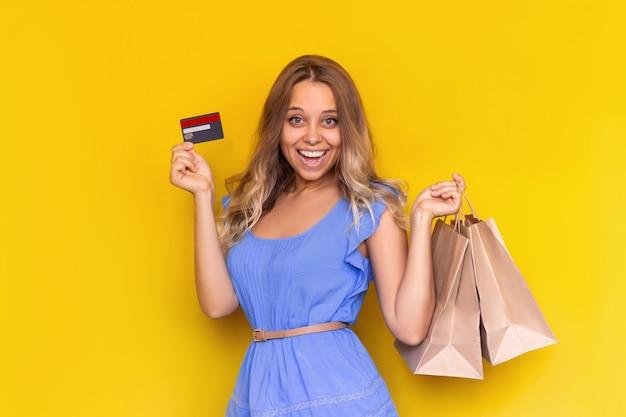 Молодая очаровательная блондинка держит в руке бумажные эко-пакеты и показывает пластиковую кредитную карту