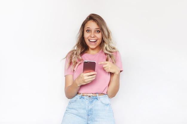 젊은 매력적인 금발 여성이 손에 휴대전화를 들고 손가락으로 화면을 가리킵니다