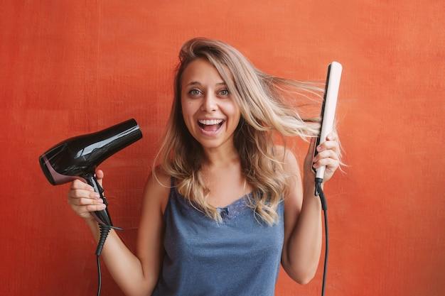 Молодая очаровательная женщина держит в руках фен и выпрямитель для волос.