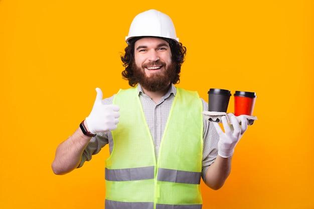 若い陽気なひげを生やしたエンジニアが笑顔でカメラを見て、2杯の温かい飲み物を持って彼がコーヒーが好きだと親指を立てている