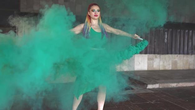 장식 조각과 무지개 아프리카 머리 띠와 메이크업 밝은 녹색 봄 드레스에 젊은 명랑 소녀. 그녀는 건물 근처에 서서 거리에서 녹색 연기를 뿜습니다.