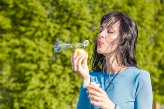 A young cheerful woman blows bubbles.