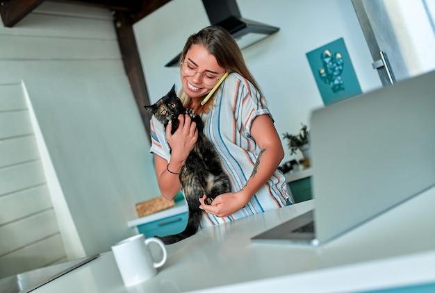 Молодая веселая женщина в повседневной одежде и очках играет с кошкой и разговаривает по телефону, работая на ноутбуке дома на своей кухне.