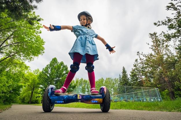 Маленькая девочка ребенка катается в городском парке на автожире. летние развлечения на природе. электросамокат - это современный экологически чистый вид транспорта. самобалансирующийся самокат