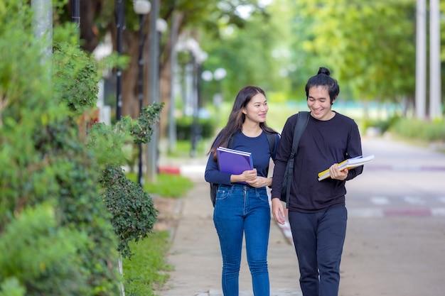 Пара молодых студентов колледжа идет на занятия. они гуляют по университетскому городку, читая книгу. осень - прекрасное время года.