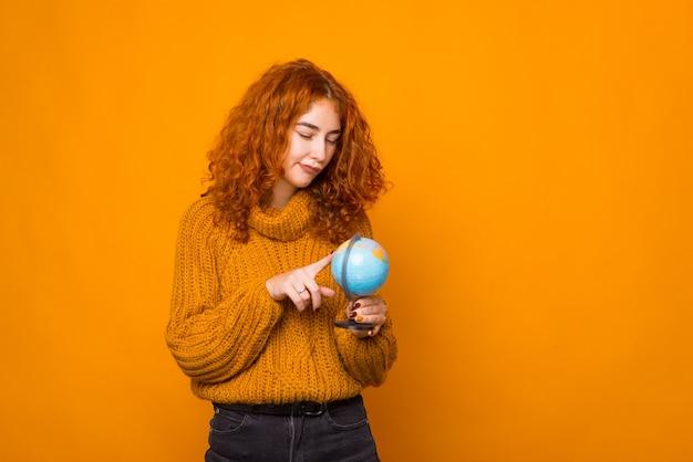 混乱している若い女性がオレンジ色の背景の近くで地球を見ています。