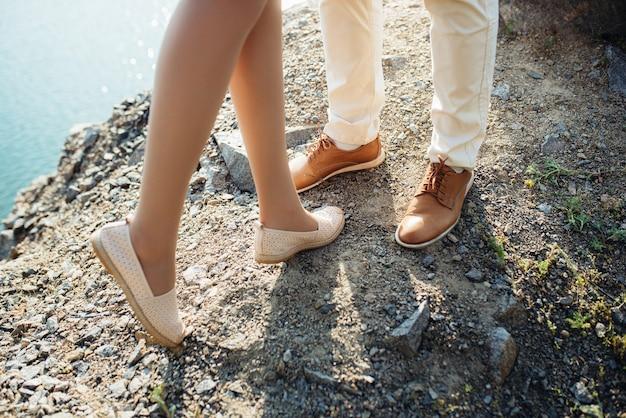 Молодая пара парень и девушка гуляют возле горного озера в окружении гранитных скал