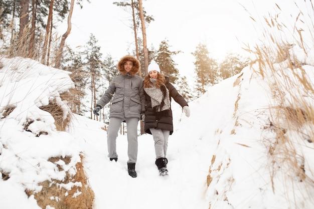 冬の雪に覆われた森を若いカップル、男性と女性が歩いています。