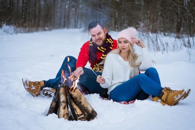 冬の若い人たちの外でキャンプファイヤーの近くの雪の中に座っている若いカップル、大人の男性と女性...