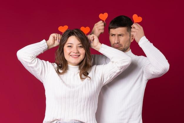 Молодая пара дурачится на красном фоне с сердечками из картона ручной работы.
