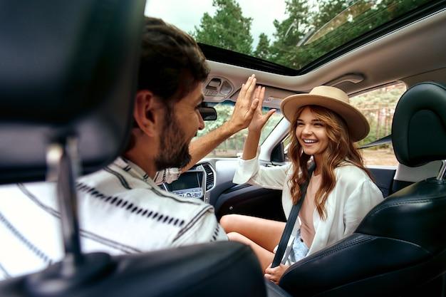 Молодая пара дарит друг другу пятерку на новой машине. мужчина ведет машину со своей девушкой и веселится. покупка и аренда авто. путешествия, туризм, отдых.