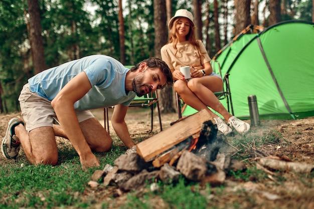 若いカップルがテントの近くのキャンプファイヤーのそばに座って、松林でコーヒーを飲んでいます。キャンプ、レクリエーション、ハイキング。