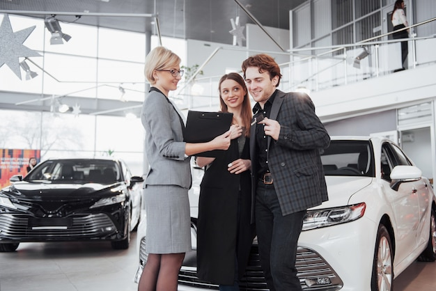 若いカップルが新しい車を買います。ディラーは彼らに署名文書を与える