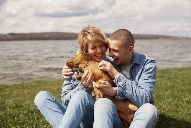 湖のほとりの若いカップルが芝生に座って犬と遊んでいます。
